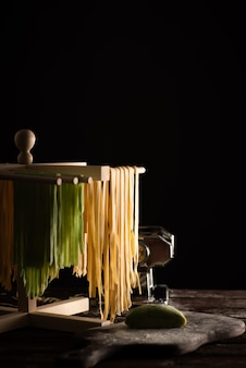 Freshly prepared tagliatelle paste is dried on a wooden drier, traditional italian cuisine