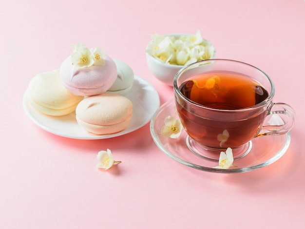 Freshly prepared tea and colored marshmallows and jasmine on a pink table. the composition of the morning breakfast.