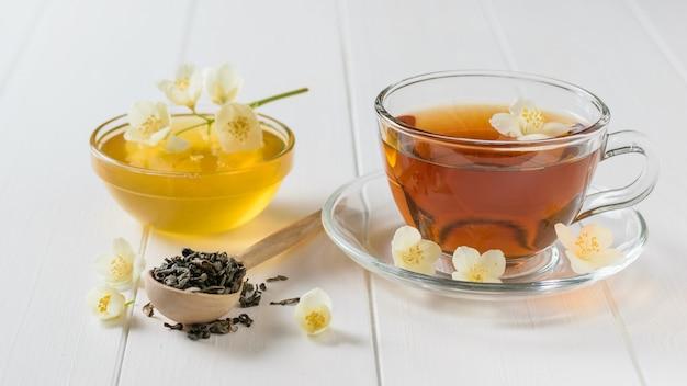Freshly prepared tea with jasmine flowers and honey on a table.