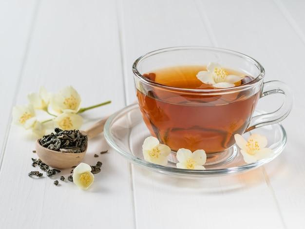 Freshly prepared tea with jasmine flowers on a table.