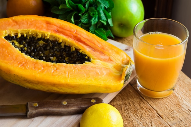 Freshly pressed papaya juice in glass, ripe halved fruit on wood cutting board