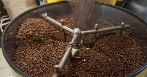 갓 볶은 아라비카 커피 콩이 회전하는 쿨러 전문 기계에 떨어지는