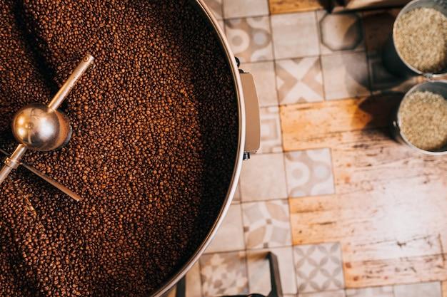 현대적인 커피 로스팅 기계를 통해 갓 볶은 향기로운 커피 콩. 위에서 보기