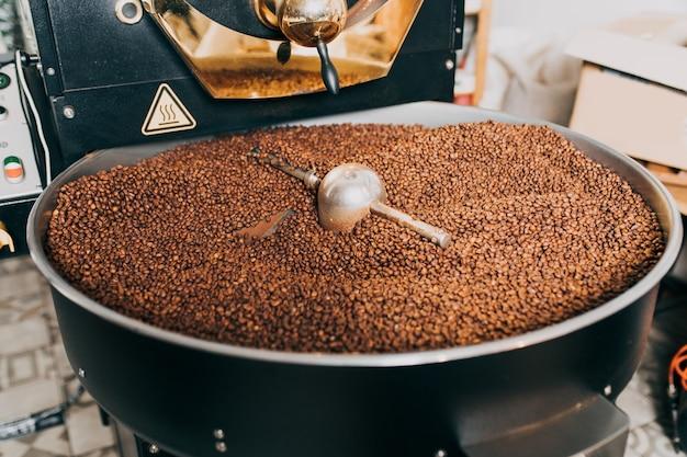 현대적인 커피 로스팅 기계를 통해 갓 볶은 향기로운 커피 콩.