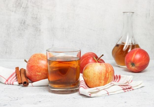 壁の背景とテーブルの上のキッチンタオルの近くのガラスに絞りたてのリンゴジュース