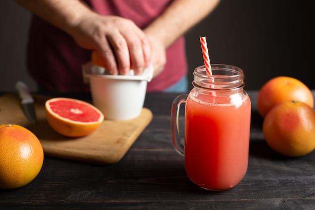 ハンドル付きの瓶に絞りたてのグレープフルーツジュース。男性の手は白いジューサーで果物を絞ります。黒い木製のテーブルの上には、丸ごとスライスされたグレープフルーツがあります。