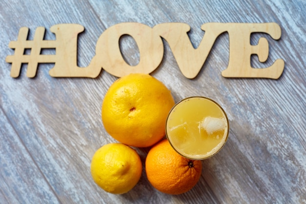 Freshly squeezed juice in a glass with ice on the table and oranges the inscription # love