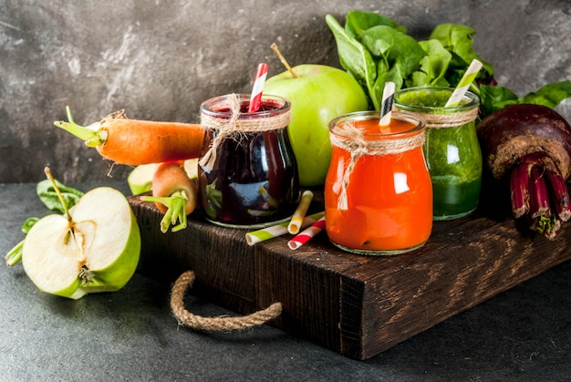 Freshly squeezed juices and smoothies from vegetables on dark stone