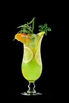 絞りたてのレモンオレンジをグラスの上にグラスに入れて、新鮮なオレンジ色の氷とオレンジのスライスを黒の背景に分離しました。