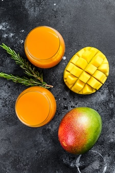 Freshly squeezed mango juice in a glass. black background.