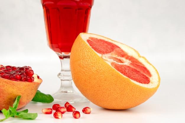 Свежевыжатый натуральный сок. свежие нарезанные плоды граната с красными семенами и грейпфрутом на белом столе. здоровое питание.