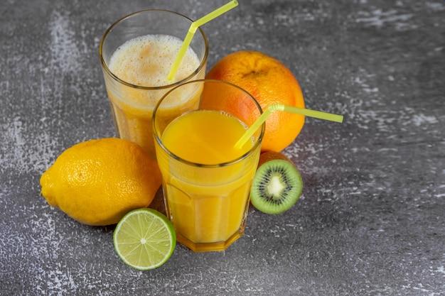 灰色のコンクリートの背景に果物に囲まれたストローで背の高いグラスに絞りたてのオレンジジュースとバナナとオレンジのスムージー。スリミングのコンセプトは、フィギュアを形にします。