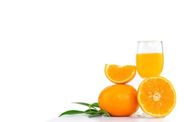 柑橘系の果物とコピースペースのあるオレンジの葉で飾られた、グラスに絞りたてのオレンジジュース。