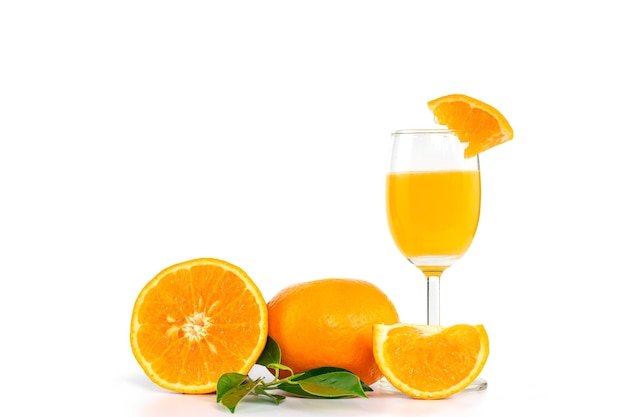 柑橘系の果物とオレンジの葉で飾られたグラスに絞りたてのオレンジジュース