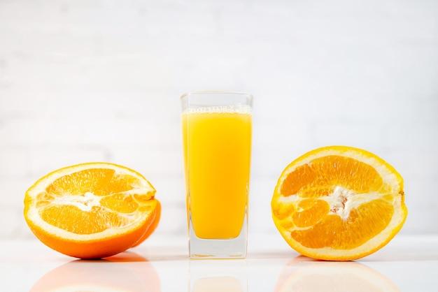 테이블에 유리에 갓 압착 된 오렌지 주스.