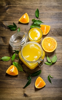 Freshly squeezed orange juice in a jar with bits of around on wooden table. top view