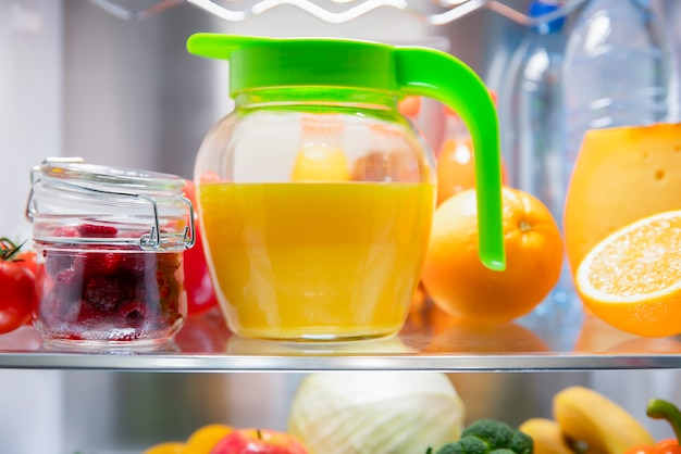 Freshly squeezed orange juice in a jug and fruit on the shelf of the refrigerator