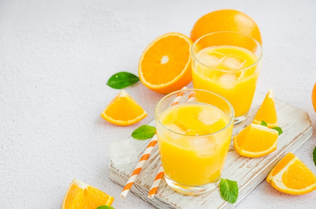 Freshly squeezed orange juice with ice in a glass and straws