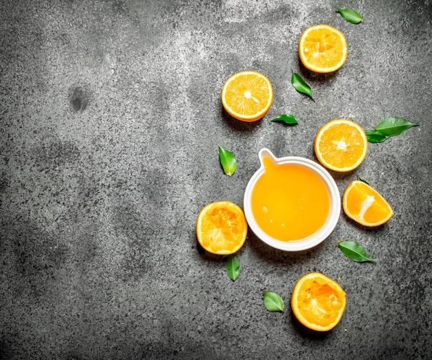 素朴な背景に果物のかけらと絞りたてのオレンジジュース