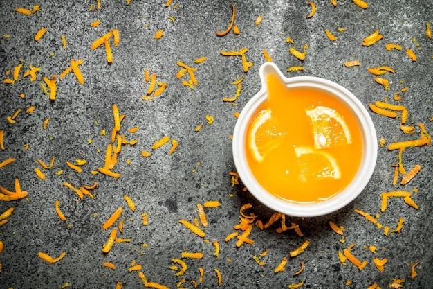 소박한 배경에 과일 조각으로 갓 짜낸 오렌지 주스