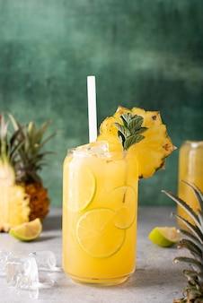 Свежевыжатый ананасовый сок с дольками лайма и льдом в стеклянных банках