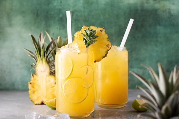 ガラスの瓶にライムのくさびと氷を入れた絞りたてのパイナップルジュース