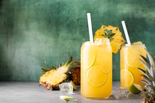Freshly squeezed pineapple juice with lime wedges and ice in glass jars