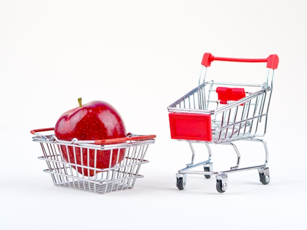 Freshness apple shopping concept with small cart and basket on the white background