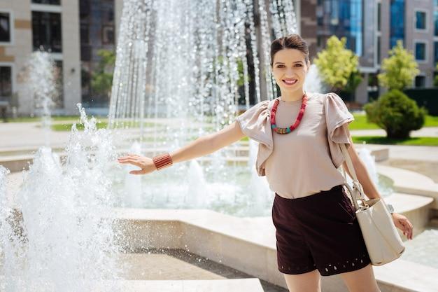 水の新鮮さ。噴水の近くに立っている間あなたに微笑んで喜んで楽しい女性