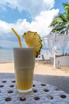 Freshpineapple frappe on the table with beach view and blue sky in summer