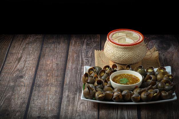 淡水カタツムリまたはリンゴガイは、木製のテーブルの上にタイのスパイシーなチリソースともち米のバスケットを使ってタイの郷土料理として調理されました