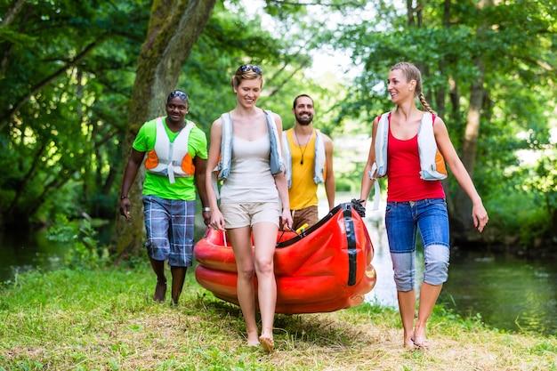 Freunde tragen zusammen kajak zum wald fluss