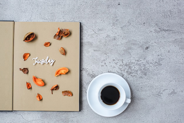 Friday flat lay minimalist autumn concept with book and a cup of coffee on grey cement background