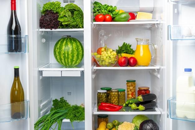 Fridge shelf full of fresh vegetables close up photo