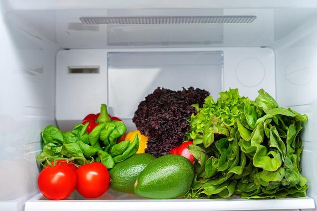 Полка холодильника полная свежих овощей крупным планом фото