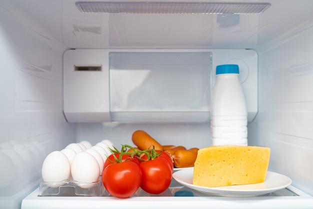 Fridge shelf with food and bottle of milk