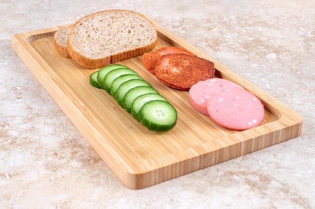 Жареные и свежие ломтики салями на деревянной доске с хлебом и огурцом.