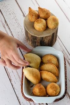 揚げてローストしたブラジルの味わい。おいしいものの1つを手に取っている女性の手。