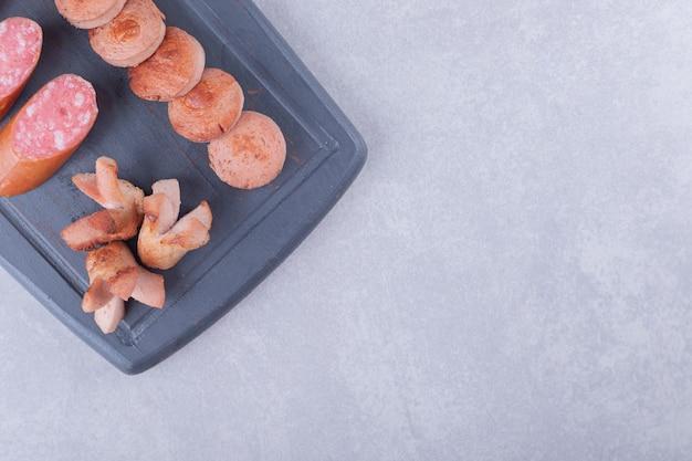 ダーク ボードに揚げて燻製にしたおいしいソーセージ。