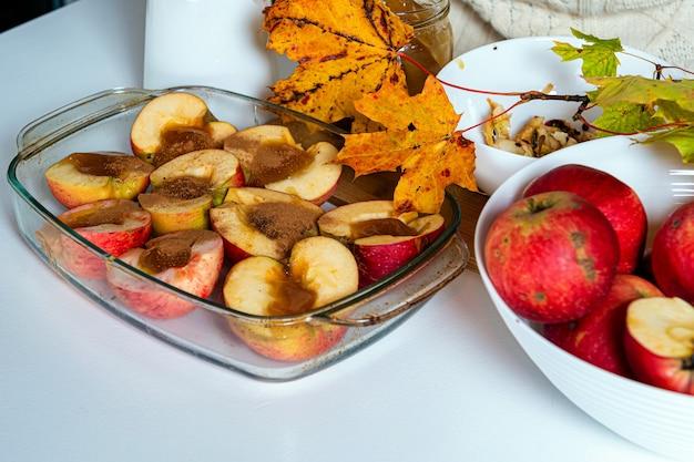 Жареные яблоки с корицей и медом, украшенные яркими осенними листьями, домашняя концепция пустыни
