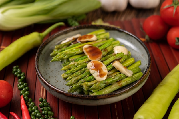 Fried asparagus with oyster sauce in a plate with bell peppers