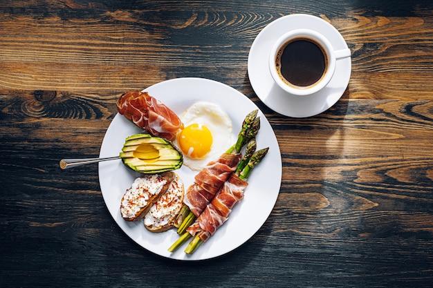 Жареная спаржа, завернутая в хамон, яичница, брускетта с мягким сыром и авокадо на белой тарелке и чашка свежесваренного кофе