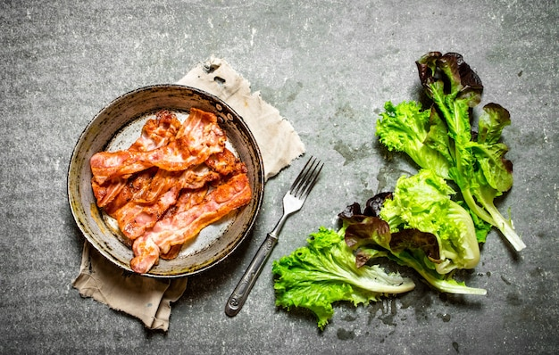 Fried bacon and greens on a stone background