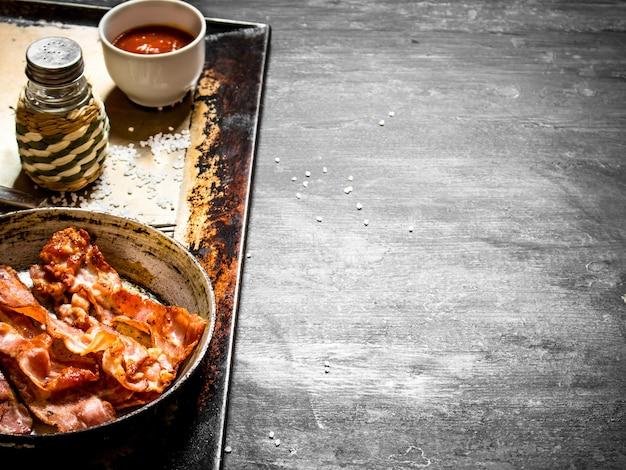 黒い木製の背景にソースとフライパンで揚げたベーコン
