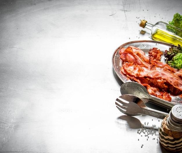 金属テーブルの上のハーブと塩と揚げベーコン
