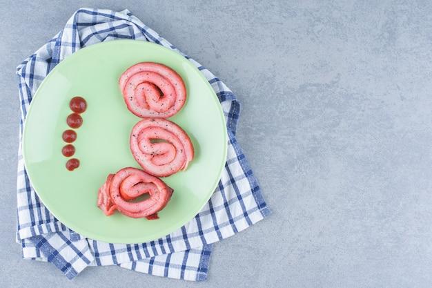 녹색 접시에 케첩과 튀긴 베이컨.