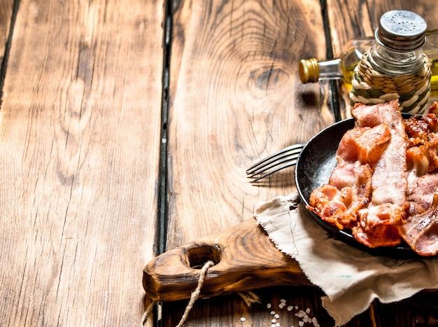 木製のテーブルの上のボード上のフライパンで塩と揚げベーコン