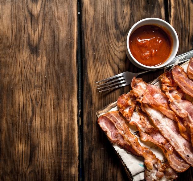 ベーコンとトマトソースの炒め物。木製の背景に。