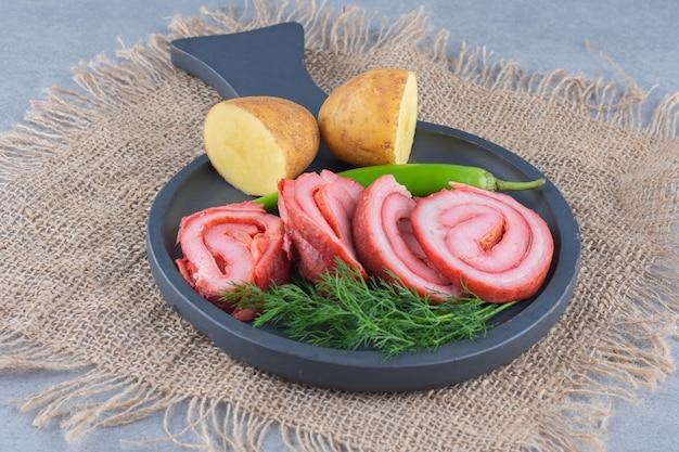 Жареный бекон на черной сковороде с овощами.