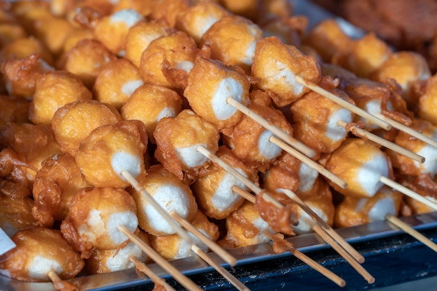 Жареные шарики во фритюре с палочками, еда в тайском стиле. уличный фаст-фуд в таиланде, крупным планом